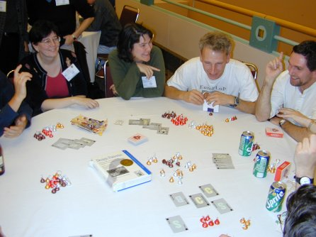 four people sitting at a round table with cards and candy