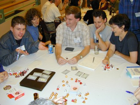 five people sitting at a round table with cards and candy