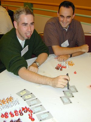 two people sitting at a round table with cards and candy